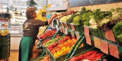 Mitarbeiterin, die Gemüse in Bedienung verkauft.