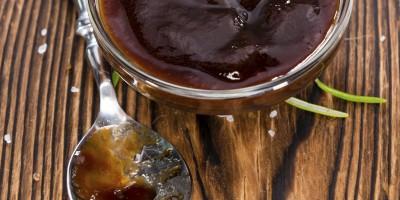 kleine Schale mit dunkler BBQ-Sauce und Löffel auf einem Holztisch