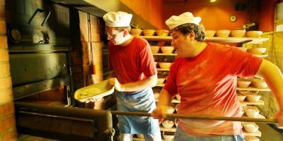 Zwei Bäcker der Eselsmühle schieben Brote in den Holzofen.
