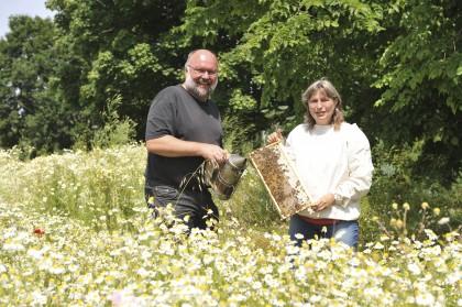 Michael Schneider und Sabine Schultz (Honigunde) stehen in einem Blumenfeld.