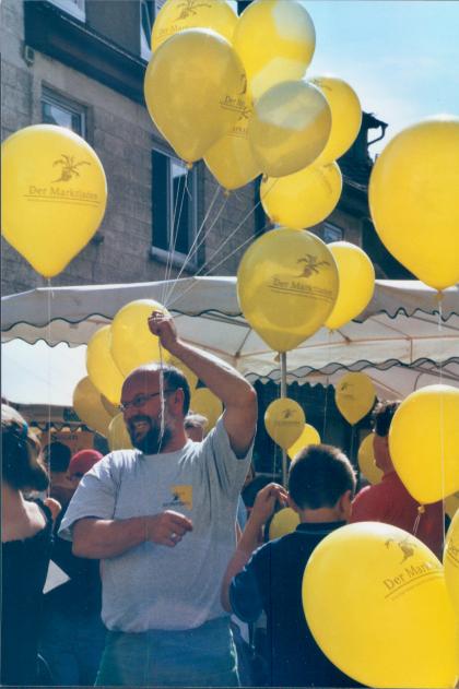 Bild von Michael Schneider mit gelben Luftballonen beim 15-jährigen Jubiläum